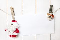 Christmas Santa Claus and snowman clothespin holding white paper Stock Photo
