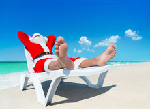 Christmas Santa Claus sunbathe on sunlounger at tropical ocean b. Each, heels at foreground - New Year travel vacation in hot countries concept Stock Photo