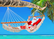 Christmas Santa Claus sunbathing in hammock at tropical palm bea Royalty Free Stock Photo