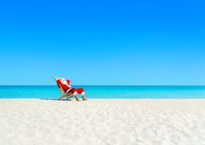 Christmas Santa Claus tan relaxing on sunlounger at sandy beach. Santa Claus tan relaxing on sunlounger at sandy tropical ocean beach. Happy New Year and Merry Stock Photography
