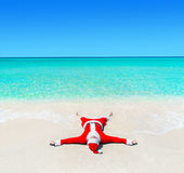 Christmas Santa Claus tanning at tropical ocean beach in waves Royalty Free Stock Images