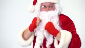 Christmas. Santa Claus on a white background in red bows for boxing and kickboxing fulfills blows. The image of a