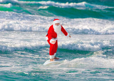 Christmas Santa Claus windsurfer surfing with surfboard at ocean Royalty Free Stock Image