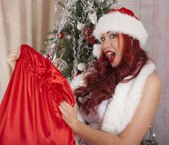 Christmas Santa girl opens bag with presents. Surprise. Beautiful smiling woman model, long curly red hair. Royalty Free Stock Photography