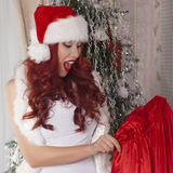 Christmas Santa girl opens bag with presents. Surprise. Beautiful smiling woman model, long curly red hair. Stock Photography