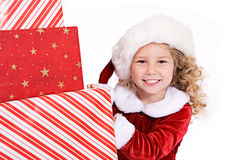 Christmas: Santa Girl Peeks Around Big Stack Of Christmas Presen Royalty Free Stock Photos