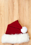 Christmas: Santa Hat Background. Background series of Christmas related items with lots of copyspace, on a wooden table setting Stock Photography
