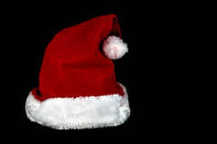 Christmas Santa Hat on a Black Background Royalty Free Stock Images