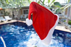 Christmas Santa hat on border of swimming pool Royalty Free Stock Image
