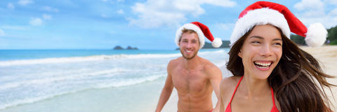 Christmas santa hat couple banner background. Happy Christmas holiday women and men honeymoon couple laughing on beach vacation wearing santa claus hats carefree royalty free stock photos