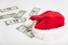 Christmas santa hat and dollars. On gray surface Royalty Free Stock Images