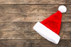 Christmas Santa hat flat lay backgrounds. With assorted xmas items red and green colors on rustic wooden table Royalty Free Stock Images