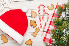Christmas santa hat, gingerbread cookies and snow fir tree Royalty Free Stock Photos