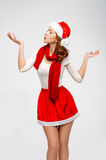 Christmas Santa hat isolated woman portrait . Looks aside on a g. Ray background.Girl in white and red clothes Stock Image