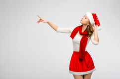 Christmas Santa hat isolated woman portrait . Pointing finger to. Wards gray background. Girl in white and red clothes Stock Photos