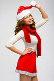 Christmas Santa hat isolated woman portrait . Smiling happy girl. On grey background. Girl in white and red clothes Royalty Free Stock Photo