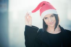 Christmas Santa hat outdoors woman smiling portrait . Smiling happy girl  wearing her Santa hat with city urban background Royalty Free Stock Image