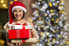 Christmas Santa hat  woman portrait hold christmas gift. Royalty Free Stock Photos
