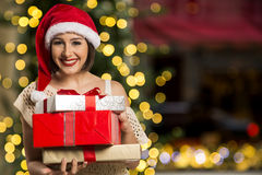 Christmas Santa hat  woman portrait hold christmas gift. Royalty Free Stock Image