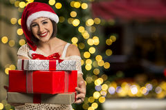 Christmas Santa hat  woman portrait hold christmas gift. Royalty Free Stock Images