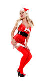 Christmas Santa Helper. Blonde dressed as Mrs. Santa in a short fur trimmed red velvet dress, white fur shrug, red stockings and black patent leather high heels stock image