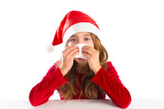 Christmas Santa kid girl blowing her nose in a winter cold. Isolated on white background Royalty Free Stock Images