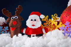 Christmas Santa and reindeer toys on snow with festive New Year balls Stock Image