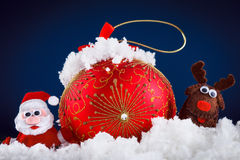 Christmas Santa and reindeer toys on snow with festive New Year balls Stock Photos