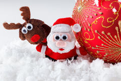 Christmas Santa and reindeer toys on snow with festive New Year balls Stock Photo