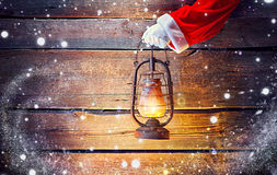 Christmas. Santa`s hand holding vintage oil lamp over wooden background royalty free stock image