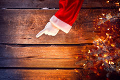 Christmas. Santa showing empty copyspace on a wooden background Stock Photos