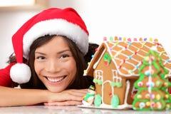 Christmas santa woman and gingerbread house. Cute young asian woman wearing santa hat stock photography