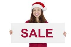 Christmas santa woman showing sale board. Christmas woman with santa hat showing sale advertisement banner Stock Photos