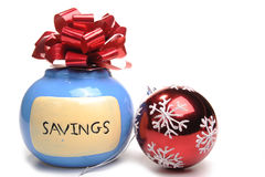 Christmas savings. Photogrpah of a money box and a christmas Bauble decoration shot in studio against a white background. the idea being christmas savings Stock Photo