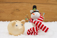 Christmas Savings,  Piggy Bank and Snowman with scarf on snow wi Royalty Free Stock Images