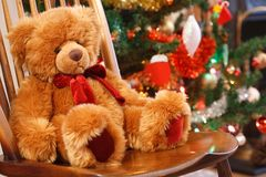 Christmas scene. Traditional Christmas scene with a teddy bear on a chair in front of a christmas tree Stock Image