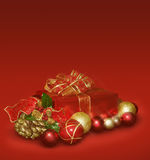 Christmas gift and balls. Red christmas gift with gold and red ornaments and balls Royalty Free Stock Photo