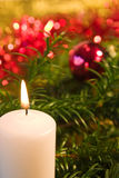 Christmas scene. Burning candle in christmas setting,focus is on the flame Royalty Free Stock Image