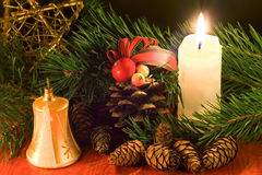Christmas scene. With golden bell, white candle and cones in low light stock photo