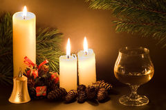Christmas scene. With white candles, cones, bell and glass of wine in low light Stock Photography