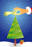 Christmas Scene. A santa claus hand put a comet star on a christmas tree Stock Images