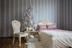 Christmas scene with a bed, Christmas tree, gifts and a chair. Christmas scene.  Bedroom with a bed, Christmas tree, gifts and a chair Royalty Free Stock Image