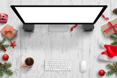 Christmas scene with computer display with isolated screen for mockup, keyboard, mouse, tea and Christmas decorations.  royalty free stock images