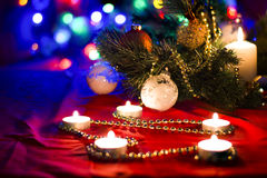 Christmas scene with decorations,fir and candles with blurry lights on background. Fir and candles on red and blue background Royalty Free Stock Photography