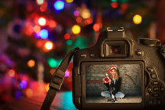 Christmas scene of a digital camera. In front of a Christmas tree Royalty Free Stock Images