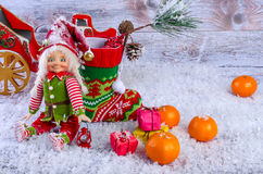 Christmas scene with elf, Christmas socks, tangerines and gifts. Royalty Free Stock Photography