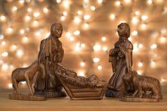 Christmas scene with figurines. Baby Jesus, Mary, Joseph on ligh Royalty Free Stock Photography