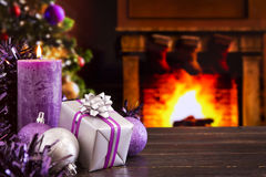 Christmas scene with a fireplace in the background. Christmas decorations, a gift and candles in front of a fireplace. A fire is burning in the fireplace and Stock Photo
