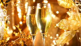 Christmas scene. Flute with sparkling champagne over holiday golden bokeh blinking background. Celebrating royalty free stock images