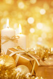 Christmas scene with gold baubles, gift and candles Stock Photo